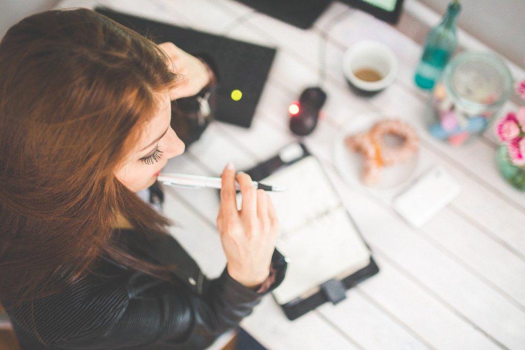 donna che studia con una penna in bocca